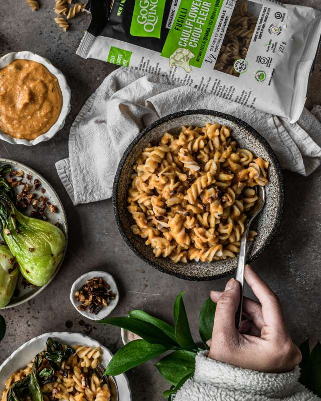 Hand and fork in a Bowl of Creamy Sweet Potato Pasta